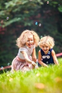 Two Girls Playing With Soap Bubbles